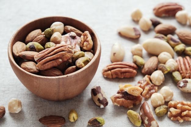 Noix mélangées dans un bol en bois, aliments sains contenant des protéines et des cétones