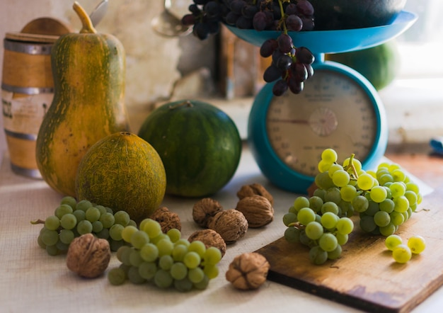 Noix, melons, pastèques et raisins à l'échelle et sur une table blanche en bois.