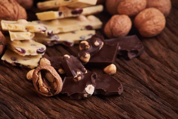 Noix et morceaux de chocolat au lait et noir sur une surface en bois