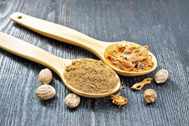 Noix de muscade moulue et arillus de muscade séchée dans deux cuillères, noix entières sur fond de planche de bois