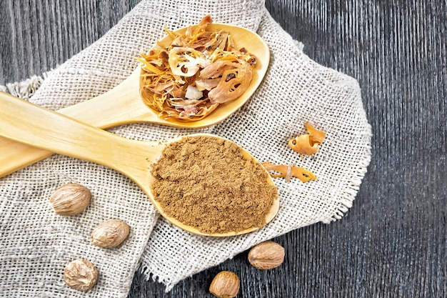 Noix de muscade moulue et arillus de muscade séchée dans deux cuillères, noix entières sur toile de jute à bord