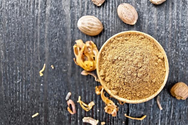 Noix de muscade moulue dans un bol, arillus de muscade séchée et noix entières sur fond de planche de bois