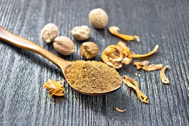 Noix de muscade moulue dans une cuillère, noix entières et arillus de muscade séchée sur fond de planche de bois foncé