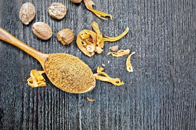 Noix de muscade moulue dans une cuillère, noix entières et arillus de muscade séchée sur fond de planche de bois d'en haut