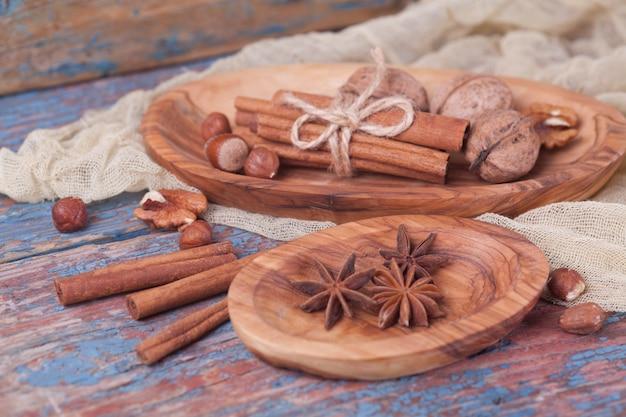 Noix et noisette cannelle anisée dans des assiettes en bois