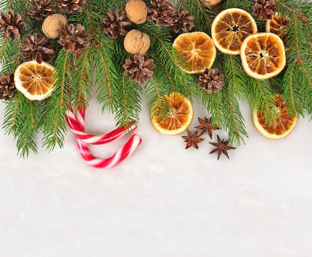 Noix, oranges séchées et cônes et branche d'épinette sur fond blanc