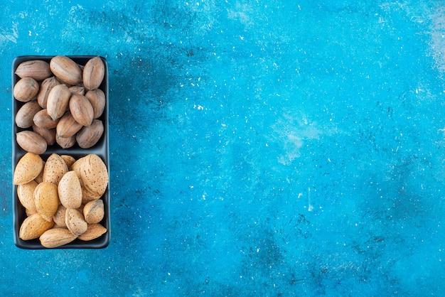 Noix de pécan et amandes dans un bol sur la surface bleue