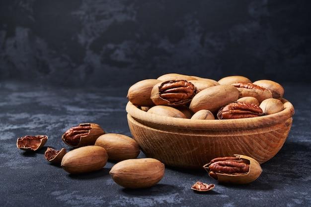 Noix de pécan dans un bol en bois