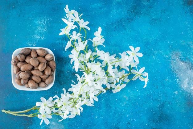 Noix de pécan dans un bol à côté de fleurs , sur la table bleue.