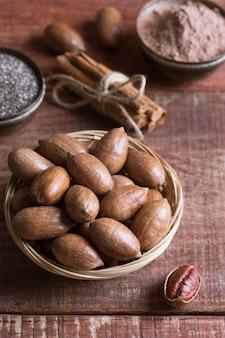 Noix de pécan, graines de chia et cacao dans des bols sur une table en bois