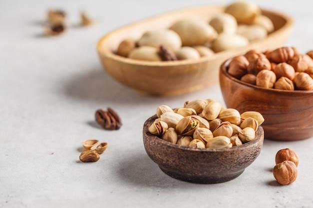 Noix de pécan, noisettes et pistaches dans un bol en bois sur un fond blanc.