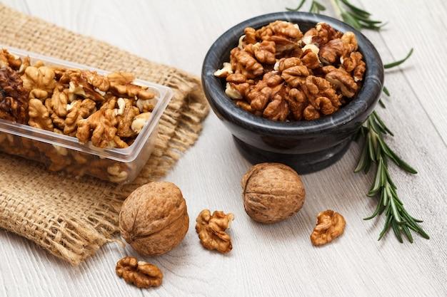 Noix pelées et non pelées dans un bol en pierre et un récipient en plastique avec un sac et du romarin sur un fond en bois. produit protéiné nutritif utile. vue de dessus.