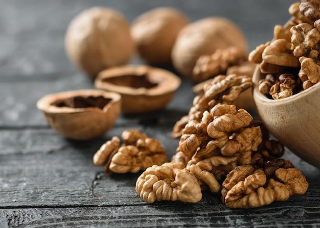 Les noix pelées sont versées d'un bol en bois sur une table en bois foncé.