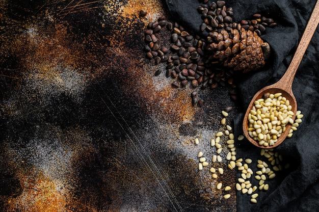 Noix de pin dans la cuillère et pomme de pin. alimentation biologique. fond noir. vue de dessus. espace pour le texte