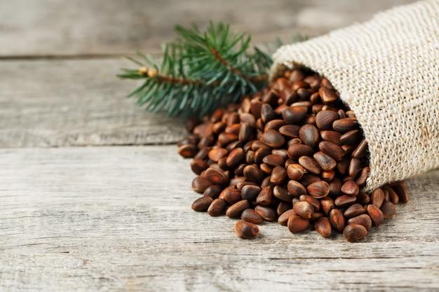 Noix de pin dans un sac de jute avec une branche vert sapin. à la campagne