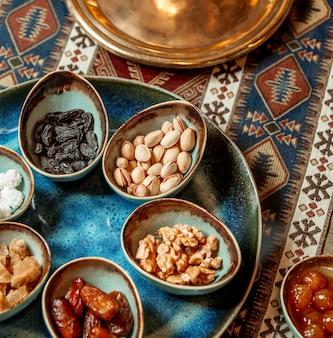 Noix pistaches kakis raisins secs dans des bols