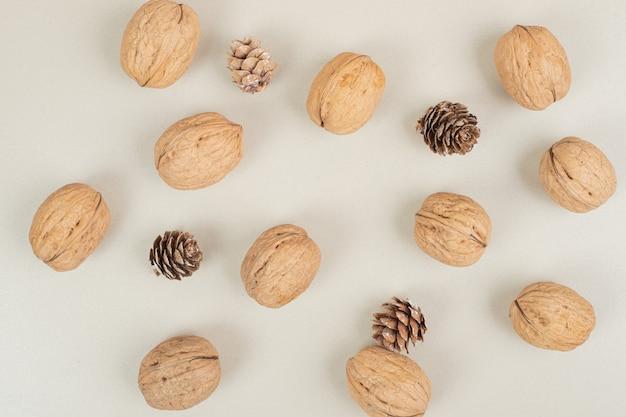 Noix et pommes de pin éparpillées sur une surface beige