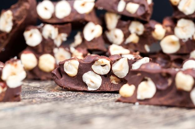 Noix et produits de cacao naturels dans la production de chocolat aux noisettes, délicieux chocolat au lait fait maison avec beaucoup de noisettes