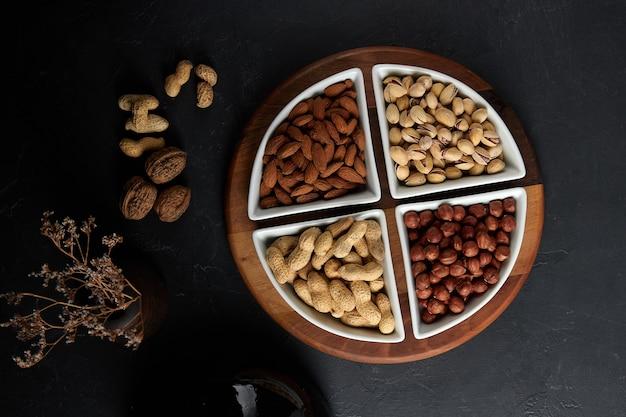 Noix saupoudrées dans des assiettes noisettes amandes pistaches cacahuètes