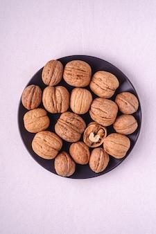 Noix en tas de nourriture dans une plaque noire avec des noix à moitié pelées sur fond blanc, vue de dessus, concept d'aliments sains
