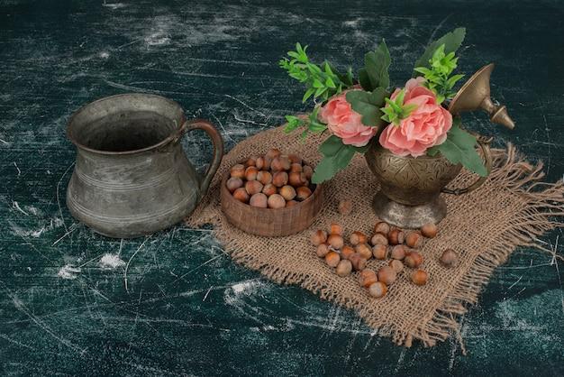 Noix avec vase de fleurs sur marbre.
