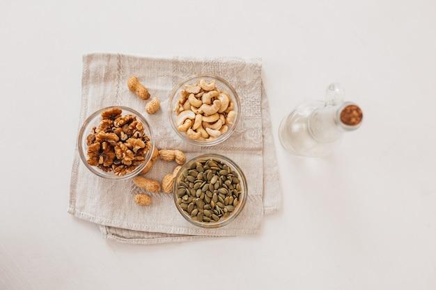 Noix et vinaigre sur un torchon en lin sur un tableau blanc. noix, noix de cajou et graines de citrouille pour une bonne nutrition. aliments sains et nutriments pour le cerveau et le corps