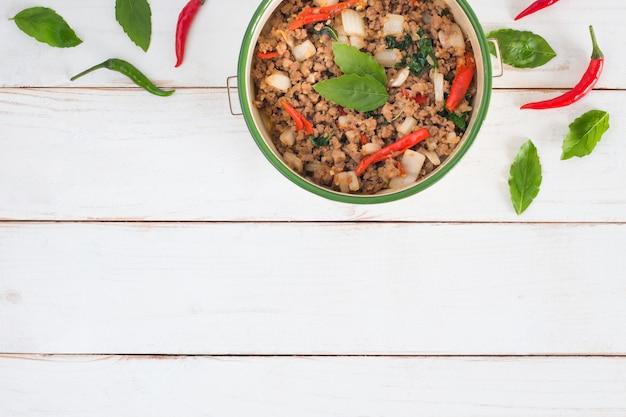Nom de la cuisine thaïlandaise pad ka prao, image vue de dessus du porc sauté aux feuilles de basilic sur une table en bois blanc