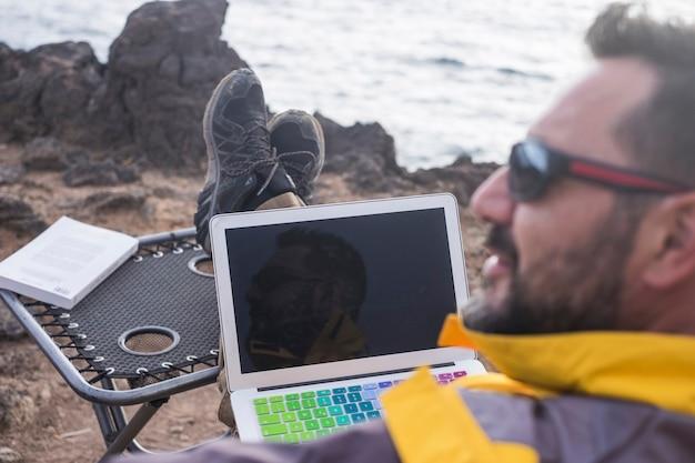 Nomade numérique au travail dans un espace ouvert alternatif de bureau inhabituel sur la côte assis près des vagues de l'océan