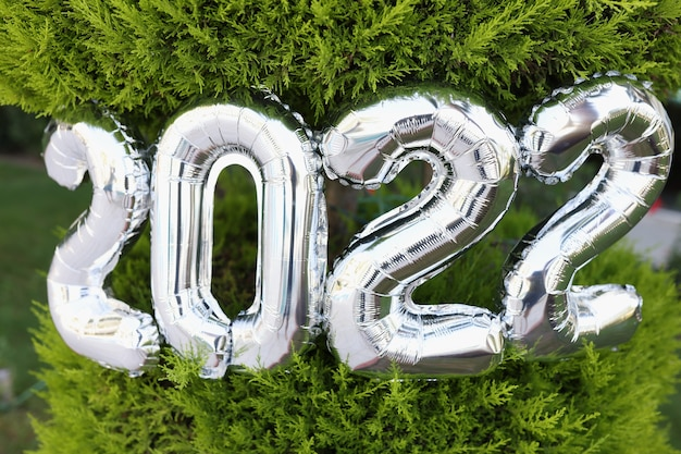 Nombre de ballons à l'hélium d'argent accrochés à un arbre de noël en gros plan