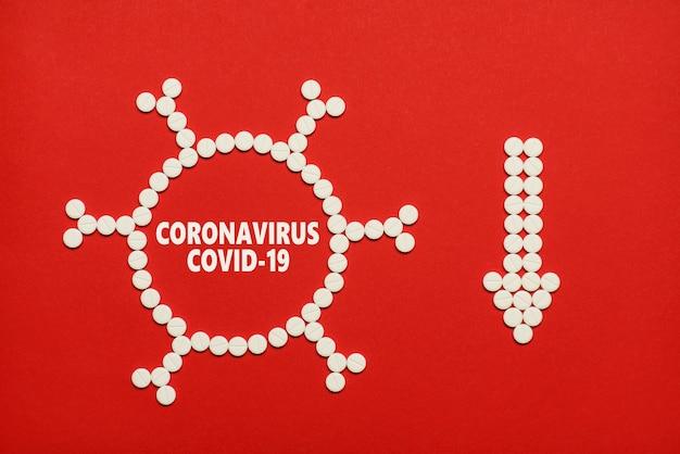 Nombre de coronavirus de personnes malades décroissant concept. haut au-dessus des frais généraux de flatlay vue rapprochée photo de comprimés en forme de virus et de flèche montrant vers le bas fond rouge isolé copie espace vide vide