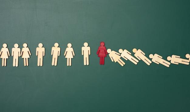 Nombre d'hommes en bois tombant sur un tableau vert. la figure rouge retient la chute. concept d'une forte personnalité, talentueux gestionnaire de crise, leader