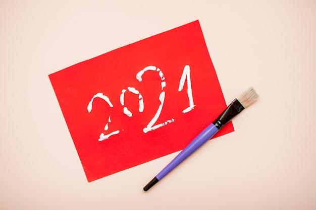 Les nombres 2021 sont écrits en peinture blanche sur une feuille de papier rouge. nouvel an