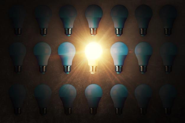 De nombreuses ampoules et une ampoule de travail reposent sur une texture de béton, vue de dessus. idée créative et penser différemment, concept