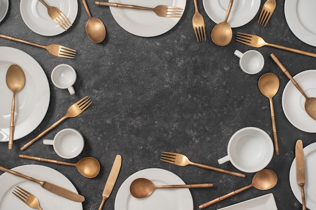 De nombreuses assiettes en céramique vide, tasses et fourchettes en laiton, couteaux et cuillères sur fond noir avec espace de copie pour votre texte.