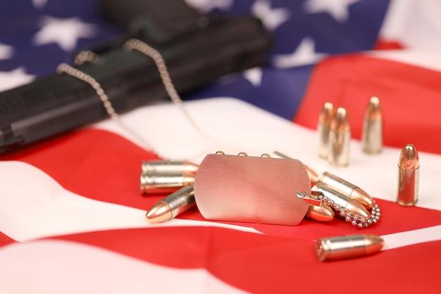 De nombreuses balles jaunes de 9 mm et des armes à feu avec des dogtags sur le drapeau des états-unis. concept de devoir et de service dans les forces de l'armée américaine. concept de vétéran