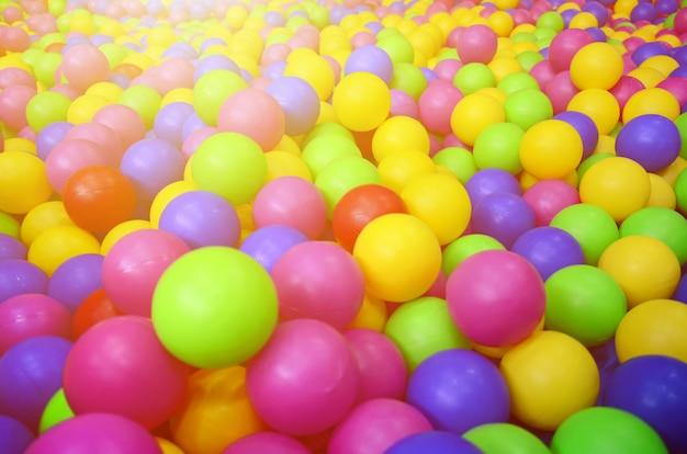 Nombreuses balles en plastique colorées dans le poste de pilotage d'un enfant sur un terrain de jeu modèle de gros plan