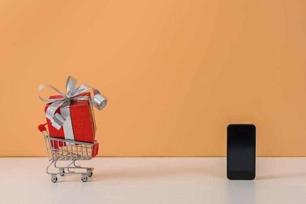 Nombreuses boîtes-cadeaux avec ruban rouge, panier à provisions ou chariot sur tableau blanc et mur orange pastel