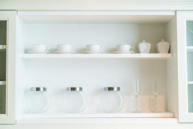 De nombreuses bouteilles en verre placées dans une armoire en bois blanche