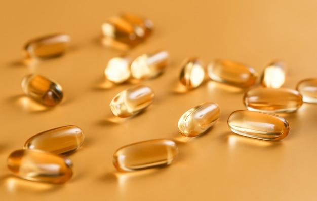 De nombreuses capsules oméga 3 sur une surface jaune
