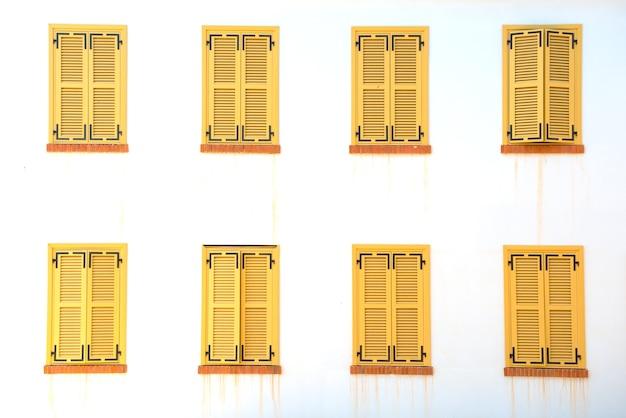 De nombreuses fenêtres fermées avec volets sur le mur blanc