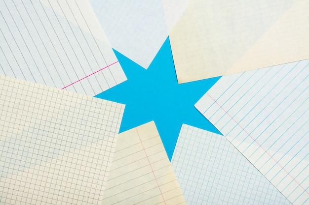 De nombreuses feuilles de cahier de nettoyage dans une cellule et une ligne forment une étoile sur un fond bleu. vue de dessus