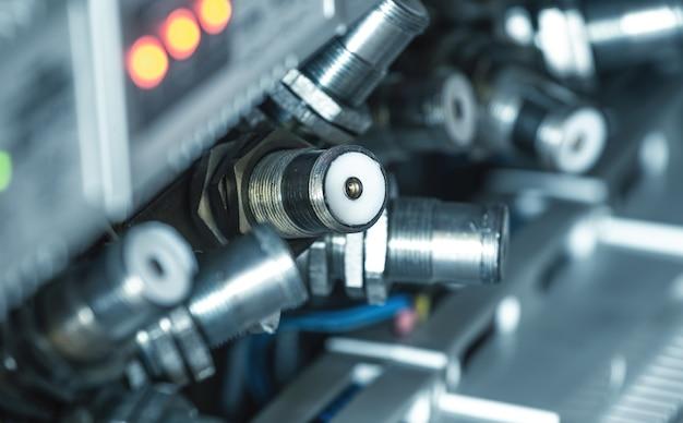 De nombreuses fiches métalliques rondes reliées les unes aux autres par des fils pendent entre des panneaux éclairés par des capteurs électroniques dans la fabrication de pièces de navires. concept de l'industrie