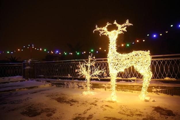 De nombreuses lampes de lumières festives en forme de cerf dans l'éclairage festif de nuit du soir. éléments décoratifs de rues en période de vacances de noël de noël