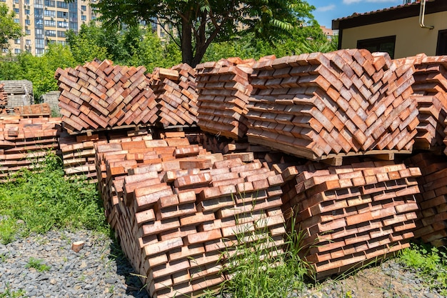 De nombreuses palettes de briques en céramique rouge sur un chantier de construction