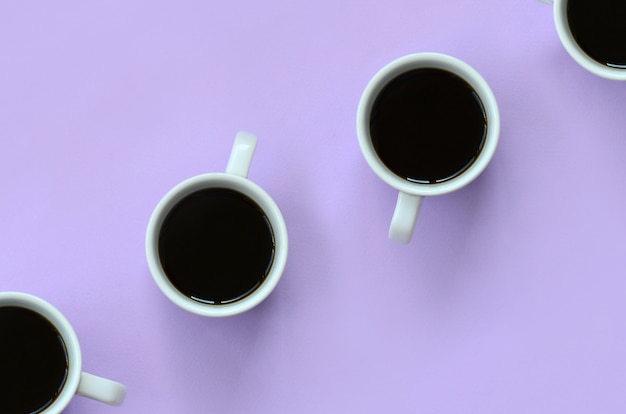 Nombreuses petites tasses à café blanches sur texture pastel violet