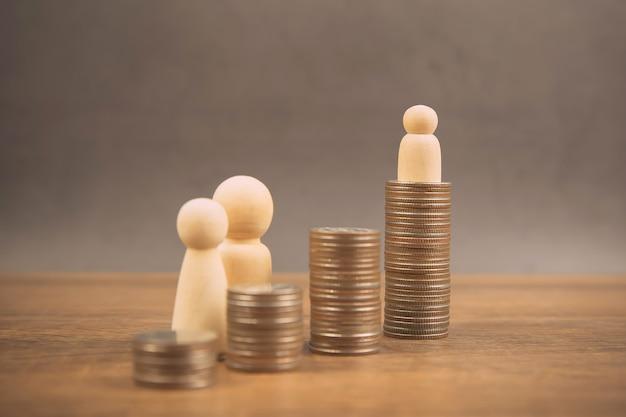 De nombreuses pièces sont empilées sous forme de graphique avec une poupée en bois familiale pour économiser de l'argent.