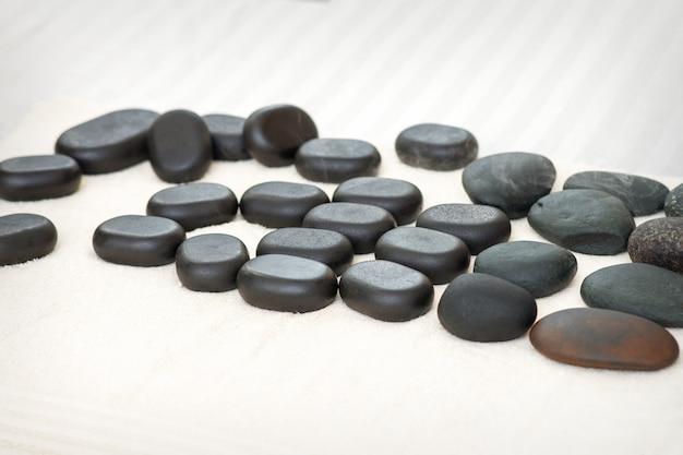 De nombreuses pierres de massage noires isolées sur la serviette sur la table