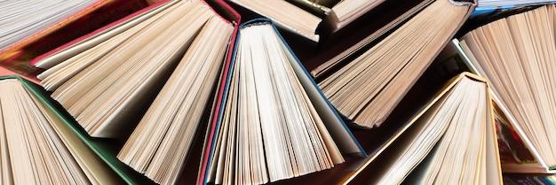 De nombreuses piles de livres. vieux livres cartonnés en arrière-plan. retour à l'école.