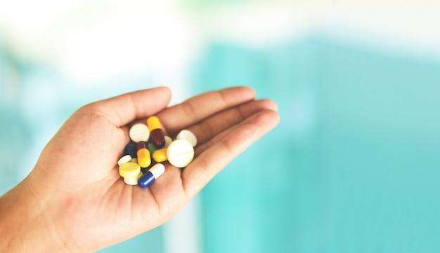 Nombreuses pilules multi couleurs en main femme