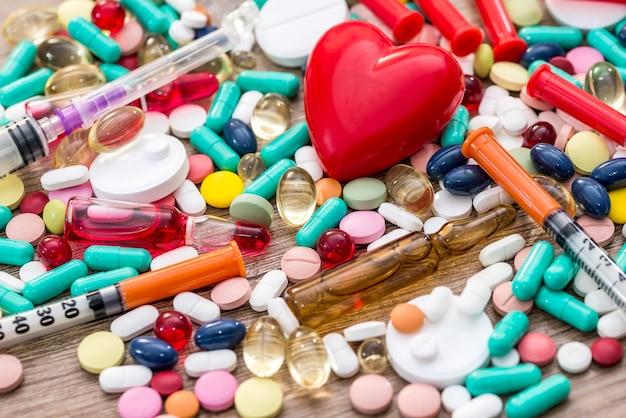 De nombreuses pilules, seringues, ampoules et cœur